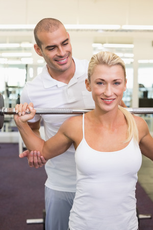 Personal male trainer helping young woman with lifting barbell in the gym photo