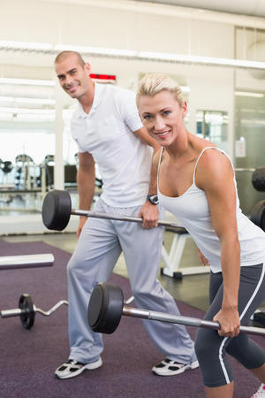 Portrait of a sporty young couple lifting barbells in the gym photo