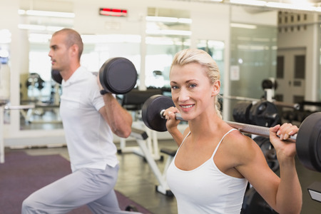Side view of a sporty young couple lifting barbells in the gym photo