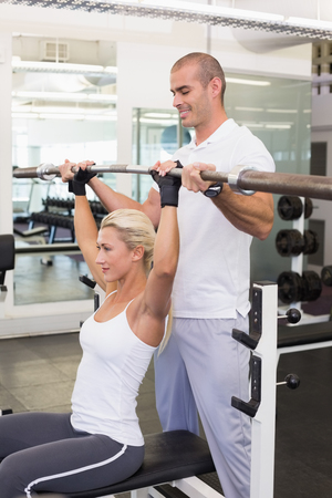weightlifting gloves: Personal male trainer helping young woman with lifting barbell in the gym