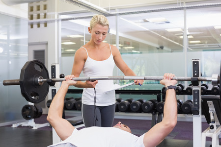 Personal female trainer helping young man with lifting barbell in the gym photo
