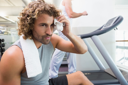 Close up of a handsome tired young man in the gym photo