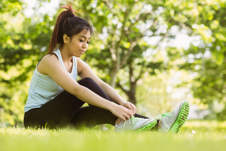 body concern: Full length of healthy young woman relaxing in park as she ties shoelace