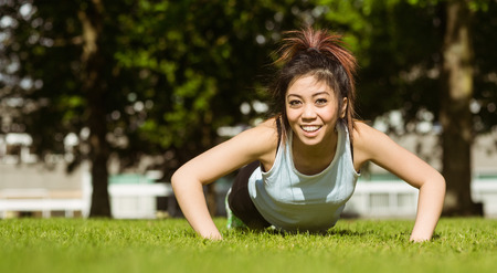 body concern: Portrait of happy healthy young woman doing push ups in park