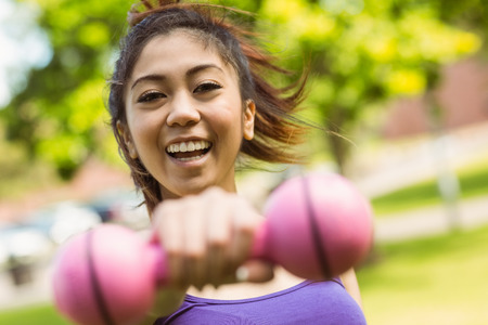 Portrait of cheerful healthy young woman lifting dumbbell in park photo