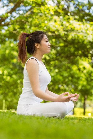 Full length of healthy and beautiful young woman sitting in lotus pose at park photo