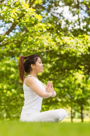 joined hands: Integral de la mujer joven y sana y hermosa que se sienta con las manos juntas en el parque