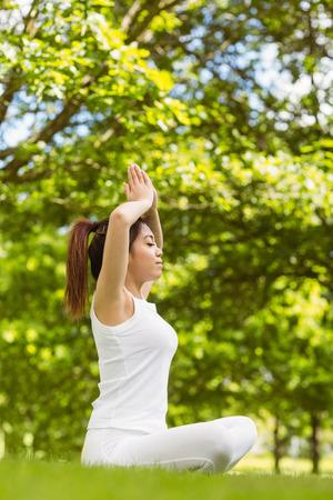 manos unidas: Integral de la mujer joven y sana y hermosa que se sienta con las manos juntas sobre la cabeza en el parque