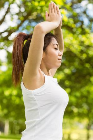 manos unidas: Vista lateral de la mujer joven y sana y hermosa con las manos juntas sobre la cabeza en el parque