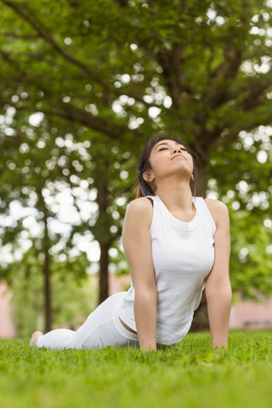 Healthy and beautiful young woman doing stretching exercises at park photo