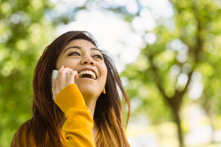 Cheerful young woman using mobile phone in the park photo
