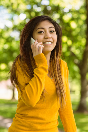Portrait of young woman using mobile phone in the park photo