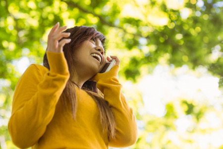 Low angle view of cheerful young woman using mobile phone in park photo