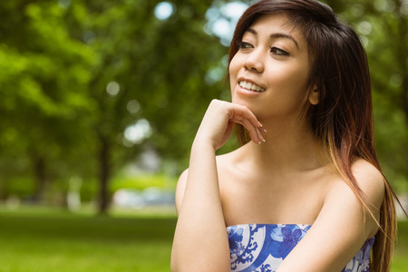 hand on the chin: Portrait of beautiful young woman with hand on chin in park