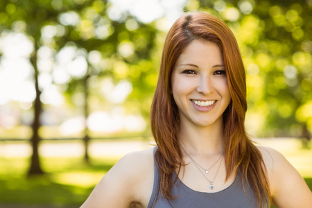 health woman: Portrait of a pretty redhead smiling on a sunny day