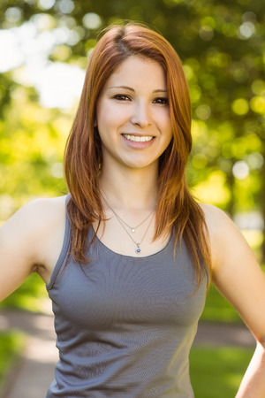 slender woman: Portrait of a pretty redhead smiling on a sunny day