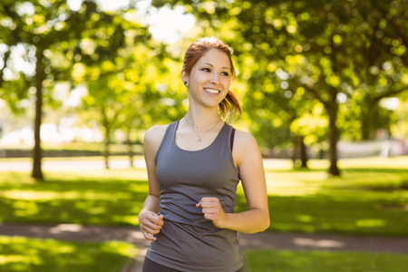 Portrait of a pretty redhead running on a sunny day