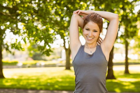 slender woman: Portrait of a pretty redhead stretching on a sunny day