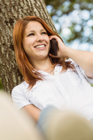 Pretty redhead smiling on the phone in park on a sunny day photo