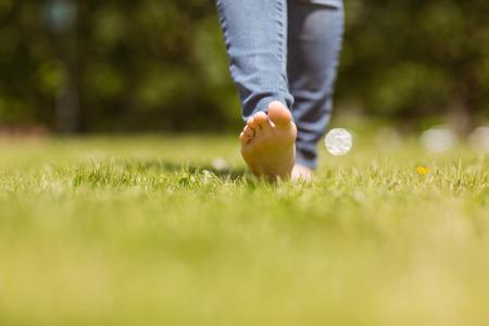 サンシャインで草の上を歩いてかなりの赤毛のクローズ アップ