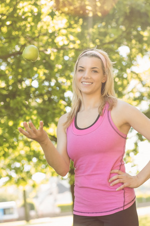 tossing: Fit blonde tossing green apple on a sunny day Stock Photo