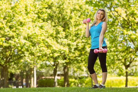 Fit blonde lifting dumbbells in the park on a sunny day photo