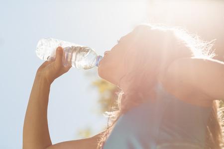 tomando agua: Montar rubia beber de su botella de agua en un d�a soleado