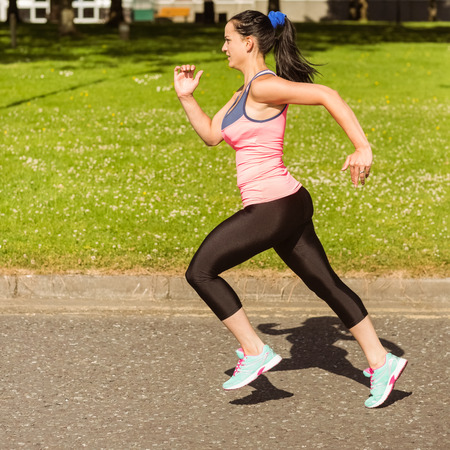 faster: Fit brunette going faster on path in the park