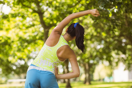 Rear view of a athletic brunette stretching in the park Stock Photo