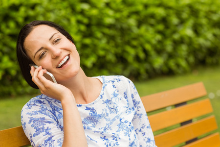 Smiling brunette sitting on bench phoning in the park photo