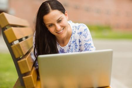 Smiling brunette lying on bench using laptop i the park photo
