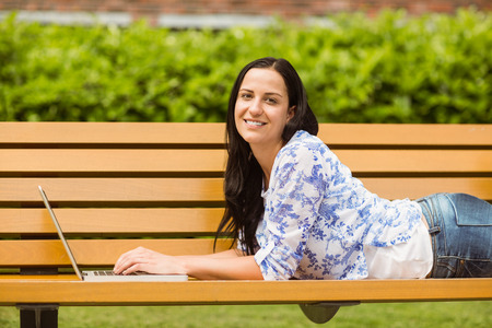 Casual brunette lying on bench typing on laptop in the park photo