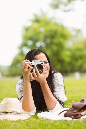 Smiling brunette lying on grass taking picture in the park photo