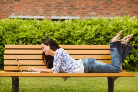 Cool brunette lying on bench using laptop in the park photo