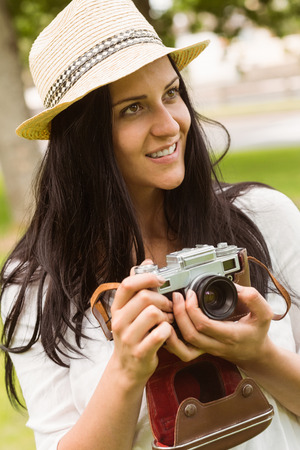 Happy brunette in straw hat holding retro camera in the park photo