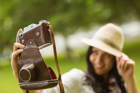 Smiling brunette taking a selfie with retro camera in the park photo