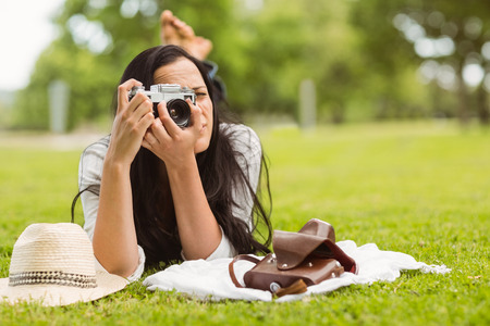 Brunette lying on grass taking picture in the park photo