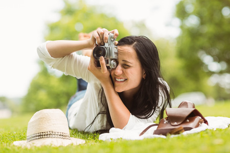 Happy brunette lying on grass taking picture in the park photo