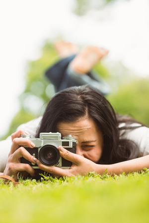 Brunette lying on grass with retro camera taking picture in the park photo