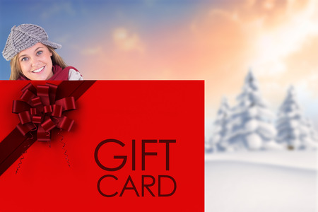Happy blonde in winter clothes showing card against snowy landscape with fir trees photo