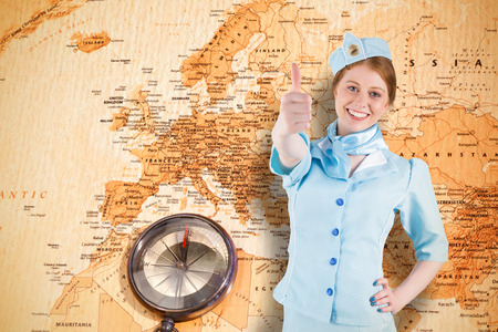 Pretty air hostess with hand on hip against world map with compass showing europe and the middle east photo