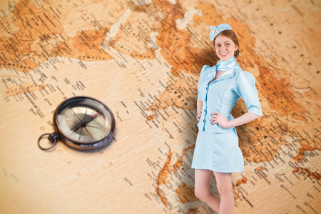 Pretty air hostess with hand on hip against world map with compass showing southern asia photo