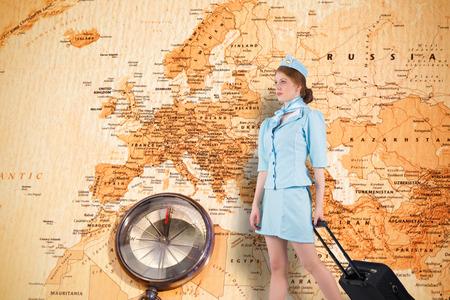 hotesse avion: Jolie h�tesse de l'air en tirant une valise contre carte du monde avec boussole montrant europe et le Moyen-Orient Banque d'images