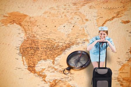 hotesse avion: Jolie h�tesse de l'air souriant � la cam�ra contre la carte du monde avec boussole montrant l'am�rique du nord Banque d'images