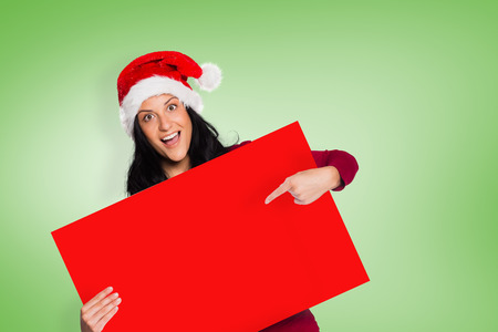 Woman pointing at sign against green background photo