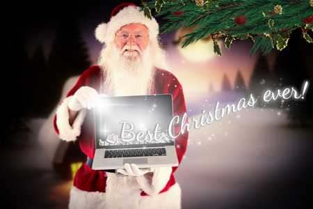 Santa Claus presents a laptop against christmas house under full moon photo