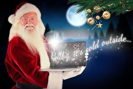 Santa Claus presents a laptop against full moon over snowy landscape photo