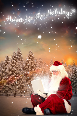 Santa sits and uses a laptop against fir tree forest in snowy landscape photo