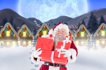 quaint: Santa carrying gifts in the snow against quaint town with bright moon Stock Photo