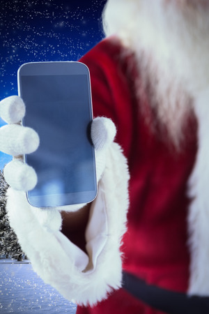 Santa Claus shows a smartphone against snowy landscape with fir trees photo